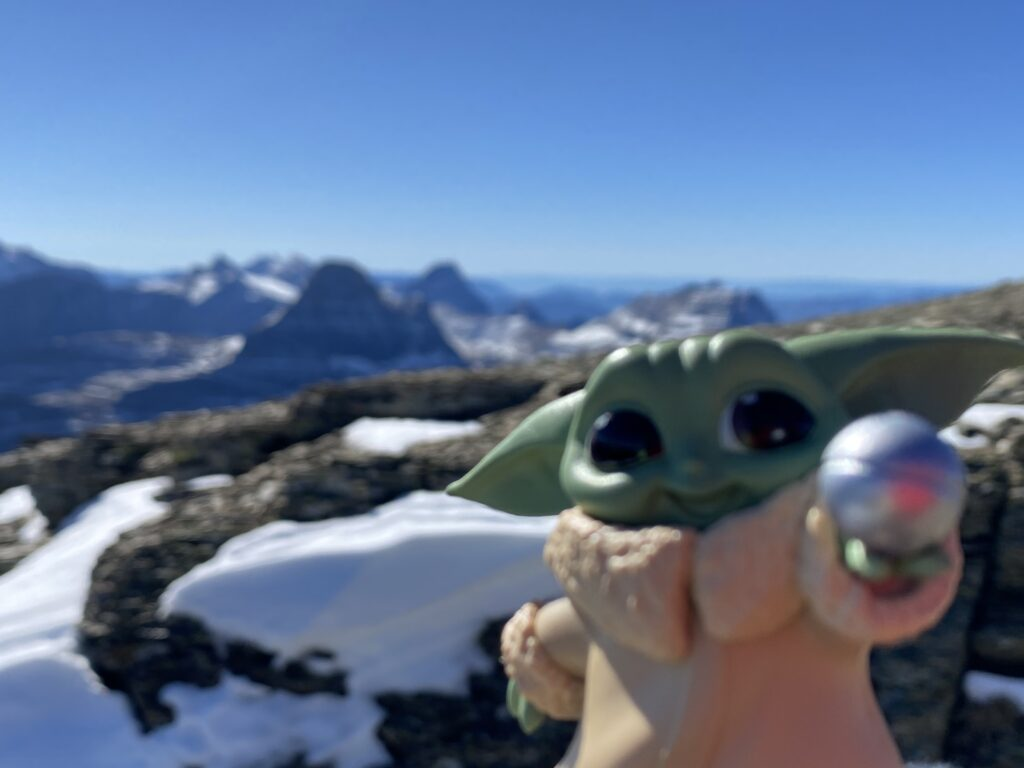 Baby Yoda toy staged on a mountain top